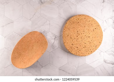 Top view of two cork plates on modern marble tiles countertop.