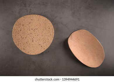 Top view of two cork plates on dark grey countertop.