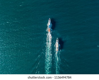 top view of two cruise ships in the open sea, one outrunning another