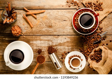 Top view of two cups of black coffee and a short of espresso with coffee bean bag, sugar, cinnamon and grounded coffee on wood background floor