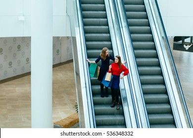 Top view of two elegant ladies to going down on the escalator.  Sale, consumerism and people concept
