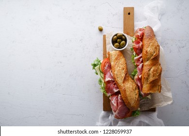 Top view of two fresh baguette sandwiches bahn-mi styled. Ham, sliced cheese, tomatoes and fresh lettuce on dark wooden cutting board on concrete background.