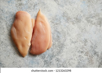 Top view of two fresh raw chicken fillets isolated on gray stone background