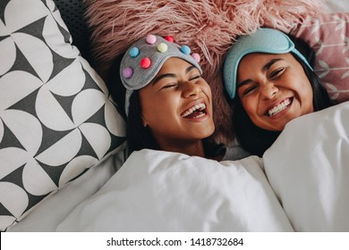 Top view of two girls laughing with eyes closed lying on bed having a sleepover. Girls with fancy sleep masks over the head laughing and having fun during a sleepover.