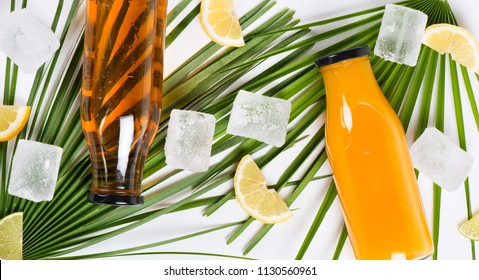 Top view of two glass bottles filled with cold juices, ice cubes and slices of fresh lemon  on green leaves of palm tree. Summer concept.