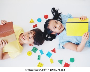 Top view of two kids with book and wooden toy over white background.