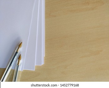 Top view of Two office pens and white sheet paper in wooden background