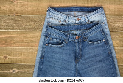 top view of two pairs of high waist women jeans front view on brown wooden background. jeans shop.