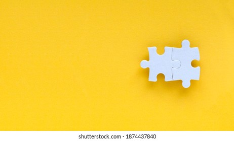 Top view two piece of white jigsaw puzzle isolated on a yellow background with copy space.