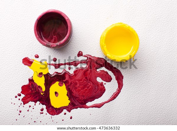 Top view of two plastic jars with paints and spilled colors on white background forming abstract art