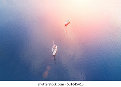 Top view of two sailboats floating in the sea on a sunny day