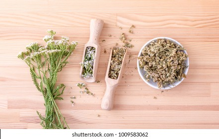 Top view of two spoons of fresh and dried flowers and leaves of yarrow with a wooden background