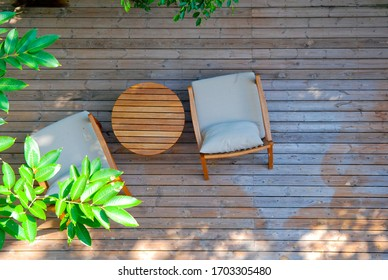 Top view of two stylish wooden chairs with cushions and a small wooden table at a balcony of a room in a resort, surrounded by garden