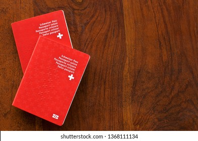 Top view of two Swiss Passports on a wooden table