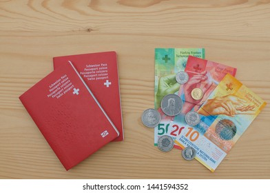 Top view of two Swiss Passports and swiss currency on a wooden table