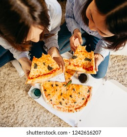 Top view of a two women sitting on the living room floor, eating pizza.