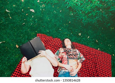 top view of two young women lying on the grass in the park with a book and earphones. Students life and outdoors leisure activities concept