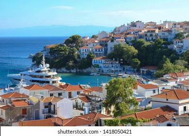 The top view of typical white architecture and big yacht in the port of Skiathos town, Skiathos island, Aegean sea, Greece