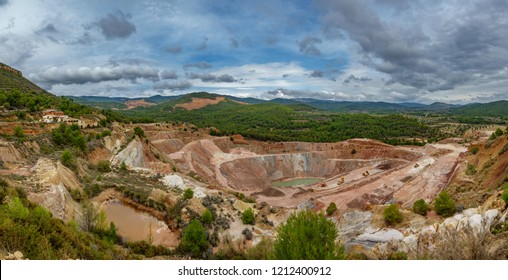 Top view ultra wide panorama of deep kaolin strip mine with dumper trucks and cranes