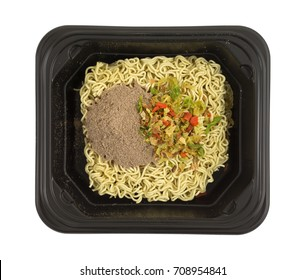 Top view of uncooked beef flavored ramen noodles with seasonings and dried vegetables in a black microwavable tray isolated on a white background.