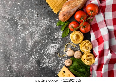 Top view of uncooked italian pasta with cheese,mushrooms,herbs,tomatoes,baguette and nest fettuccine on a dark background