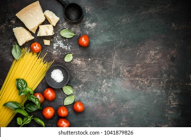 Top view of uncooked pasta with cheese and tomatoes with basil on dark rough background.