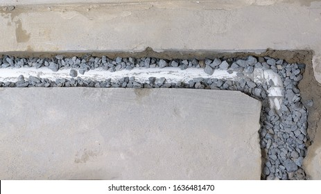 Top view of an unfinished french drain partially covered with drainage rocks