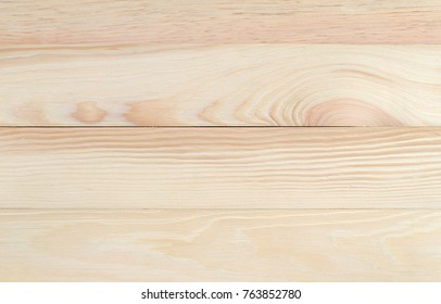 Top view of an unfinished pine table top with a gap in the wood.