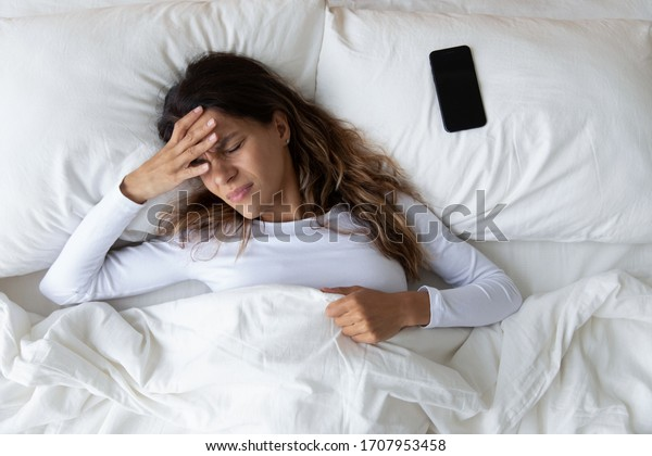 Top view unhappy woman feeling headache after sudden awakening by phone call, message signal or alarm in early morning, exhausted young female suffering from insomnia or migraine, lying in bed