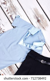 Top view of uniform for school girl. Girls brand cotton blouse and pleated skirt for school on old wooden background, top view.