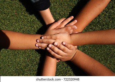 Top view united hands of children  on green grass background. Togetherness and support, children friendship.