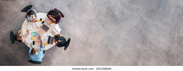 Top view of university students sitting at a table studying and working on laptop