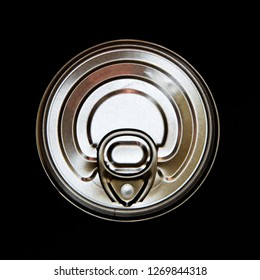 Top view of the top of an unopened aluminium food can with the tab, against black background.