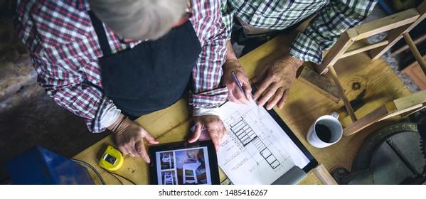 Vue de dessus d'un couple âgé méconnaissable travaillant dans un atelier de menuiserie