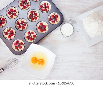 Top view of unripe muffins with ingredients. Two yolks, flour and milk placed on wooden white table. Space for text in the lower right corner.