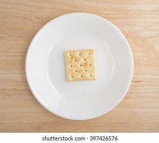 Top view of an unsalted saltine cracker on an off white plate atop a wood table top.