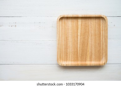 Top view of unused brand new brown handmade wooden dish plate on white wooden table background