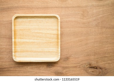 Top view of unused brand new brown handmade wooden dish plate on wooden table background