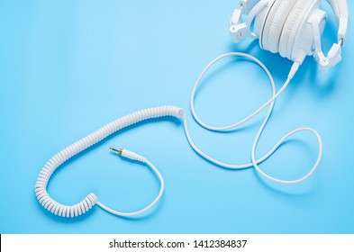 top view upon gadgets on blue background, composition from the headphones and cord in shape of heart