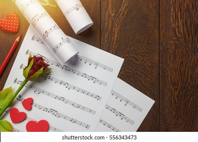 Top view valentines day love song music background and decorations.heart shape,music note paper,flower on wooden with copy space.Create this music note paper myself.