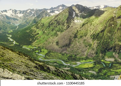 Top view of the valley between the high mountains in which flows a meandering river flowing from the upper multinskoe lake