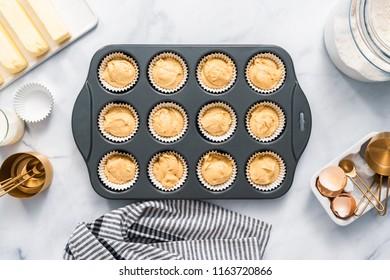 Top view. Vanilla cupcake batter in cupcake pan.