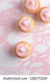 top view vanilla cupcakes with pink frosting