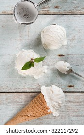 Top view vanilla ice cream in waffle cone with utensil on wood background.