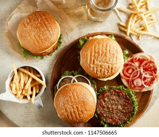 Top view of variety of burgers with fried potato and glass of beer