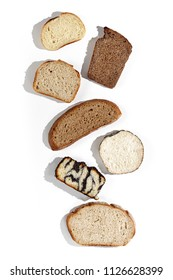 Top view of a variety homemade loaves of sliced rye, wheat, whole grain and seeds bread on white background. Bakery close-up hard light