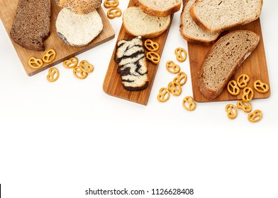Top view of a variety homemade loaves of sliced bread on wooden cutting board and salted pretzels on white background. Bakery flat lay with copy space