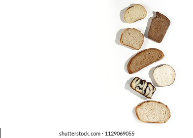 Top view of a variety homemade loaves of sliced rye, wheat, whole grain and seeds bread on white background. Bakery hard light flat lay with copy space