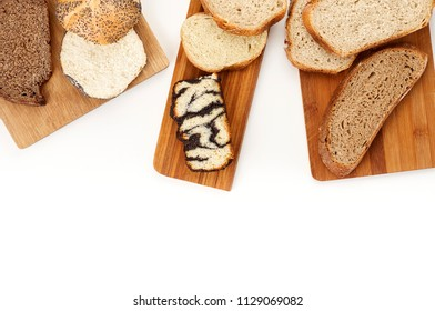Top view of a variety homemade loaves of sliced rye, wheat, whole grain and seeds bread on wooden cutting board on white background. Bakery flat lay with copy space