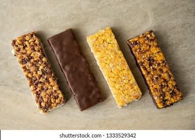 Die große Auswahl an Müsli- und Müsliriegel. Verschiedene Energy-Protein-Stangen auf Marmor-Hintergrund. Set aus Energie-, Sport-, Frühstück- und Eiweißbarren